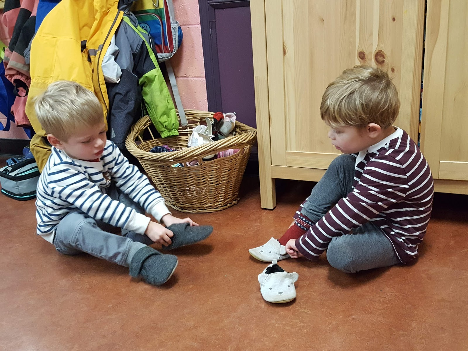 Two young boys putting on slippers