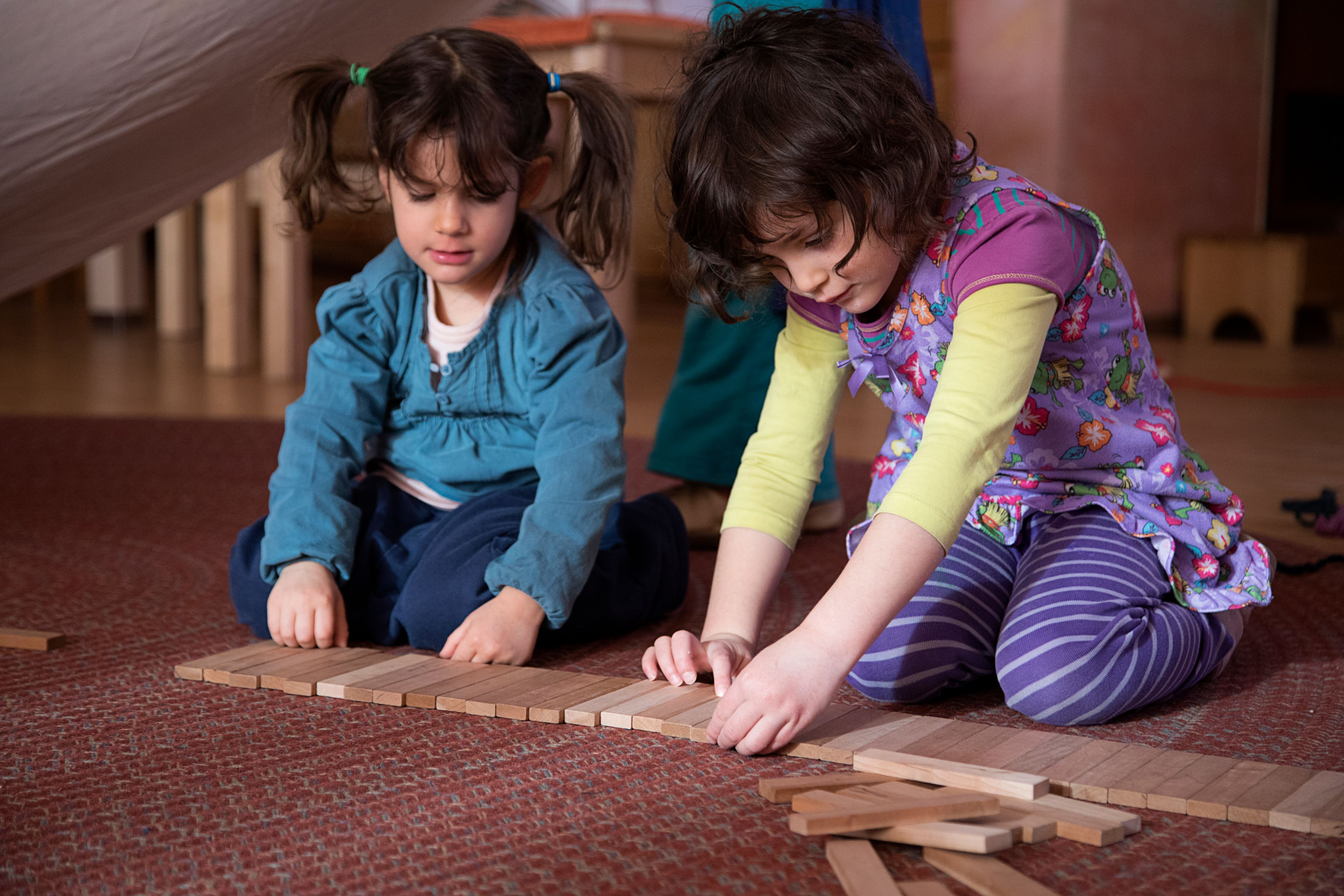 Two girls playing with wooden blocks