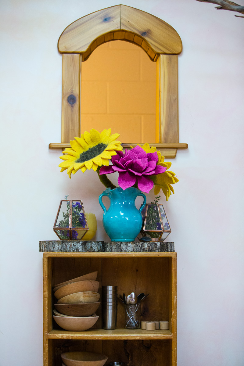 Interior window felt flowers on shelf with small plates and cups