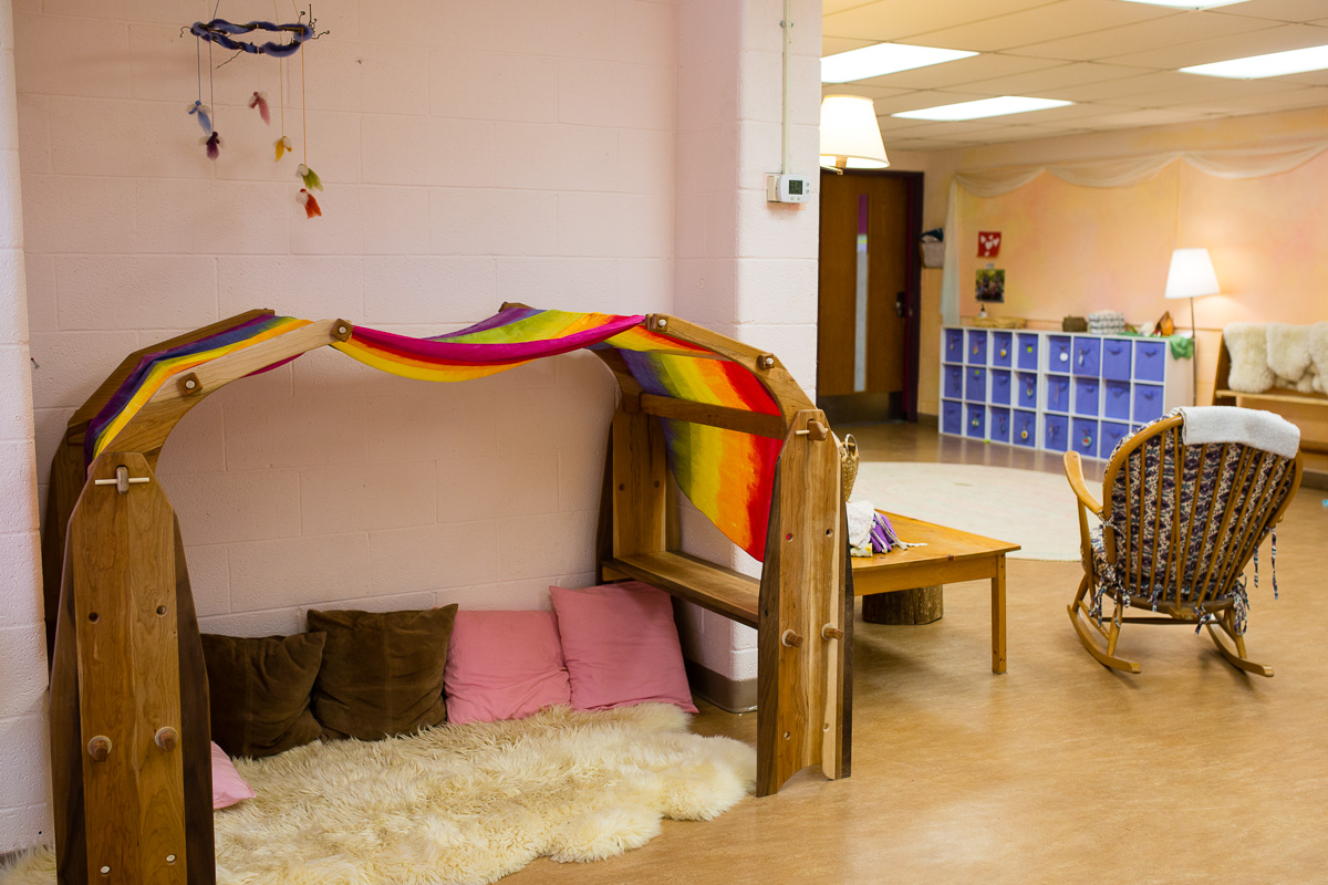 Indoor play area with silk-scarf-covered wooden toys