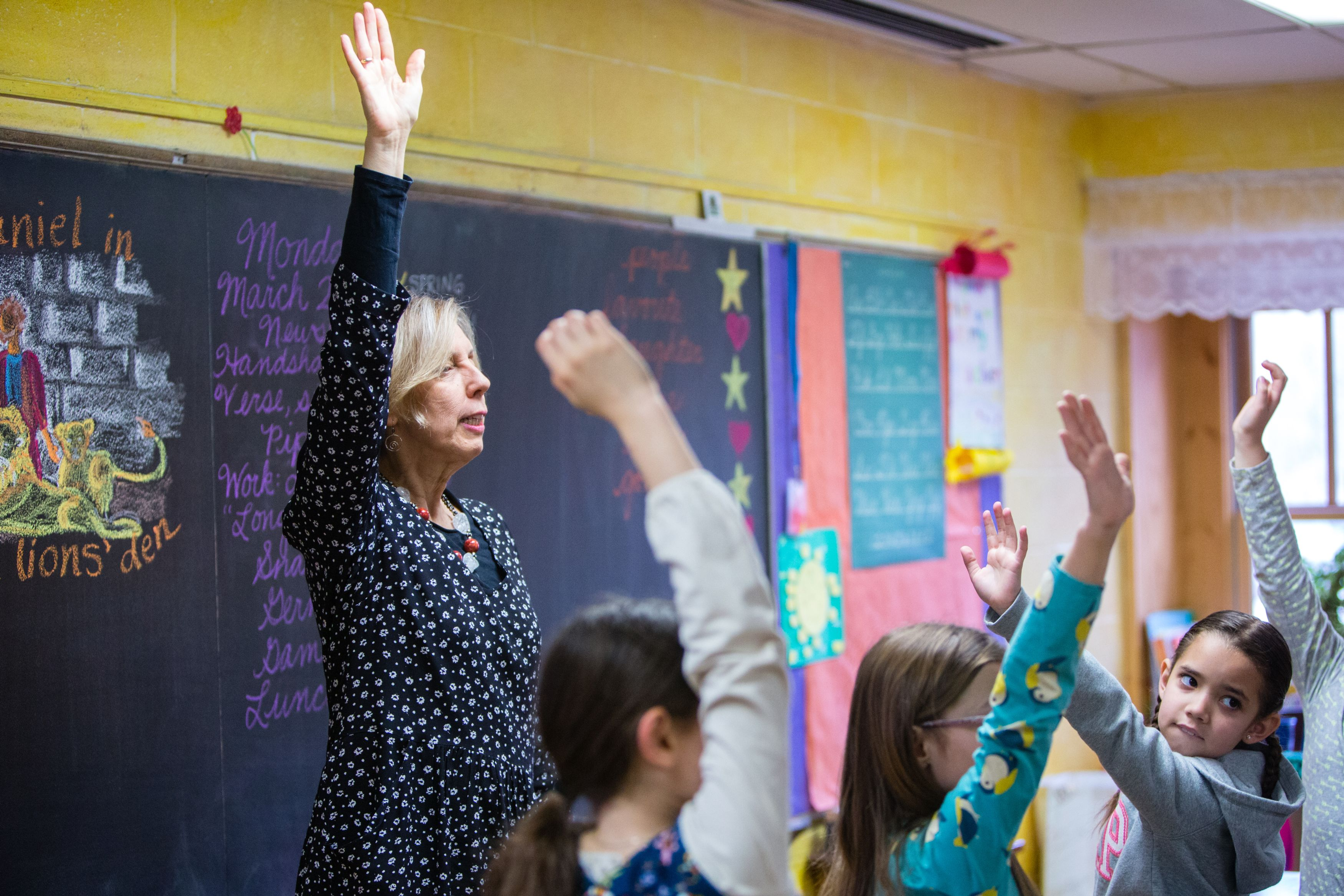Teacher and students raising hands at front of classroom