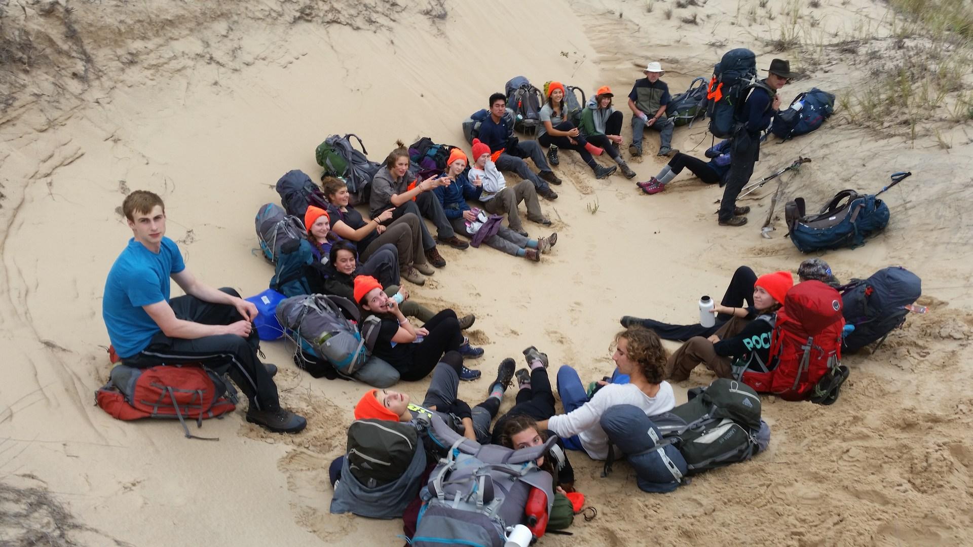 Hiking Club Laying on Beach