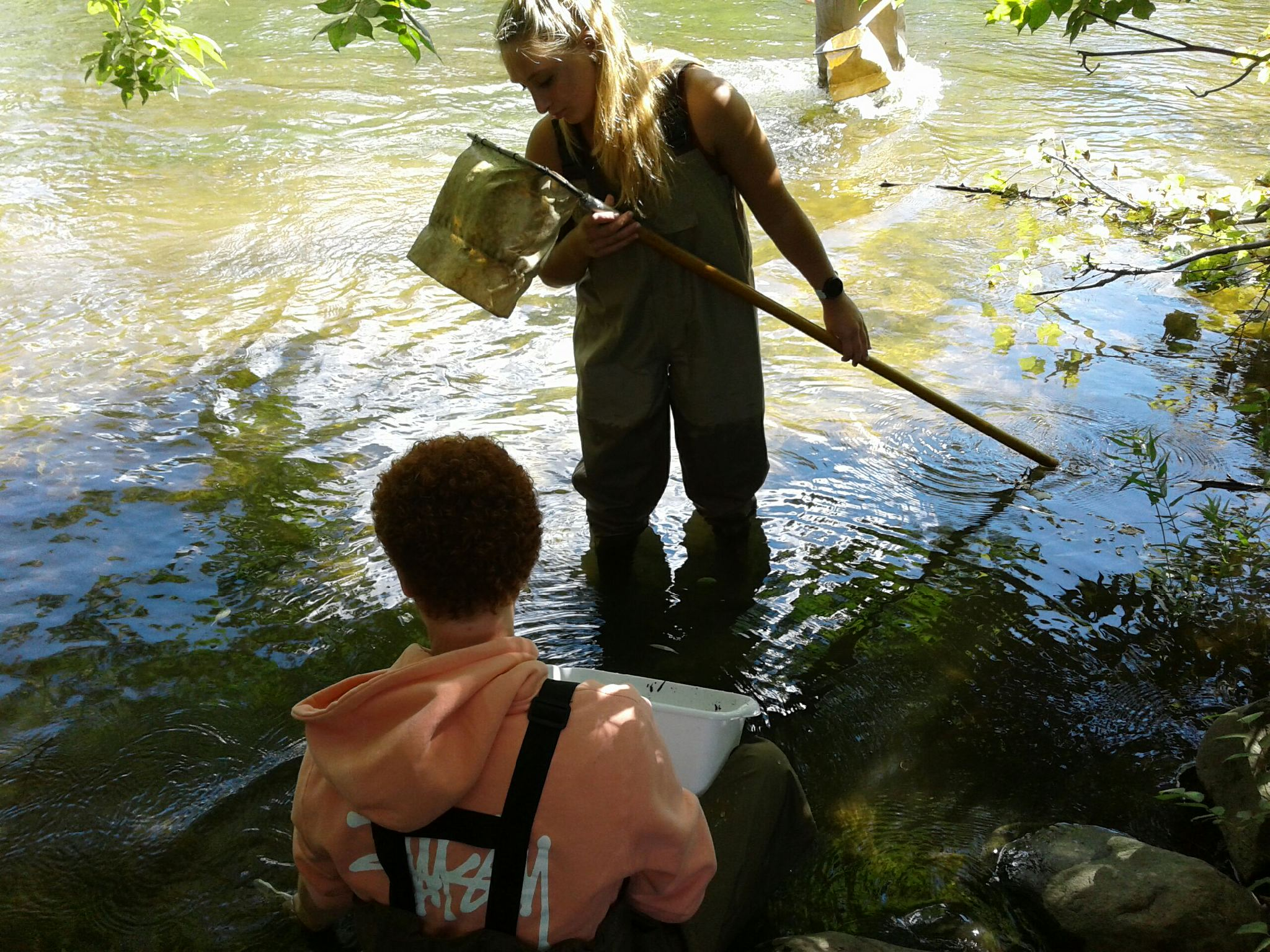 Girl and boy in river with net