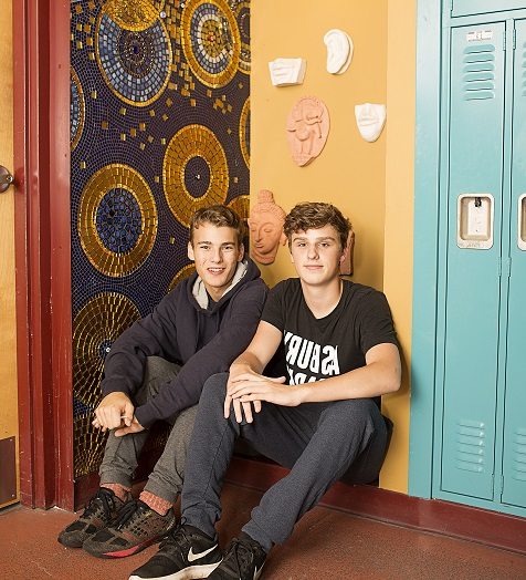 Two boys sitting next to lockers