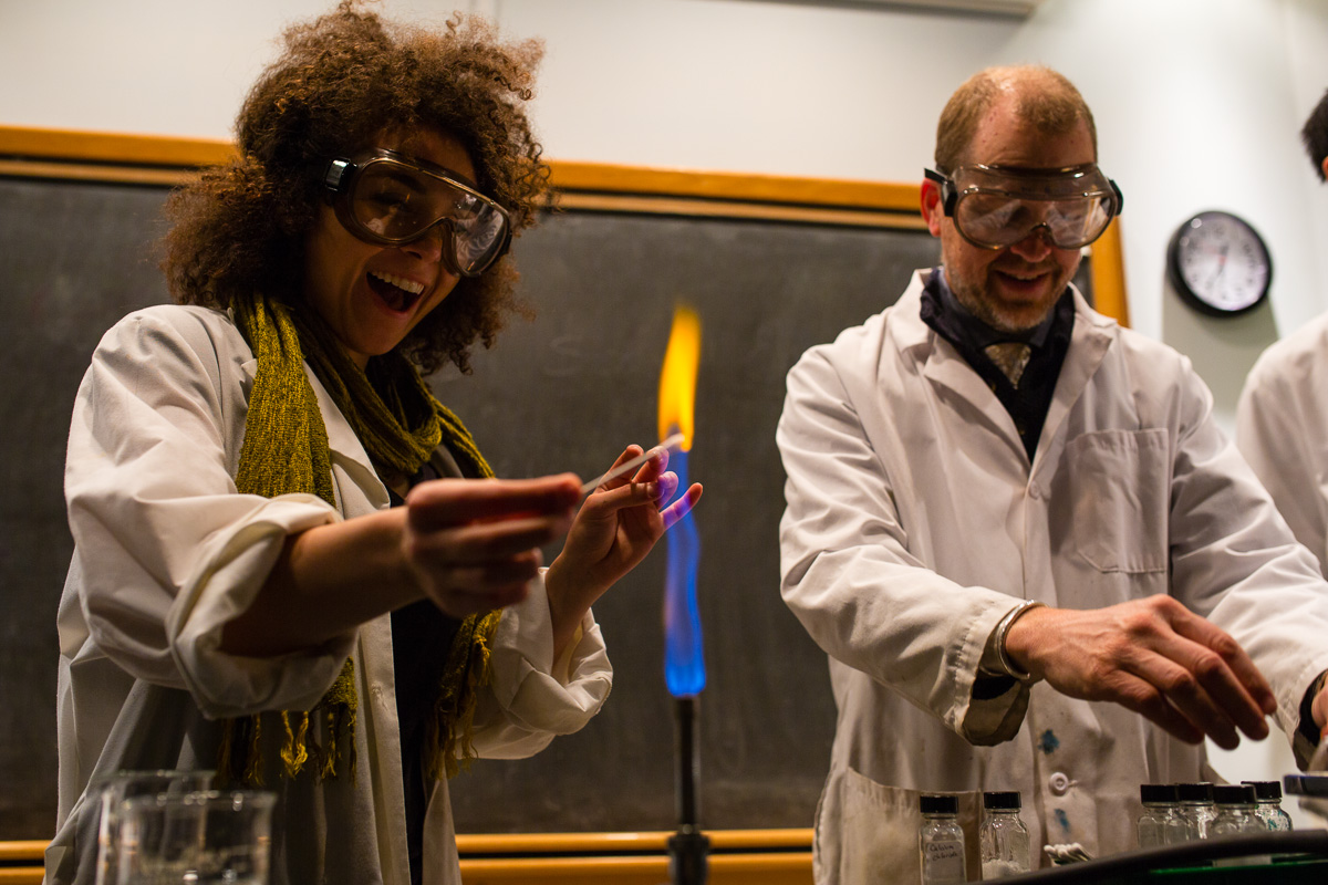 Student lighting Bunsen burner with teacher in background