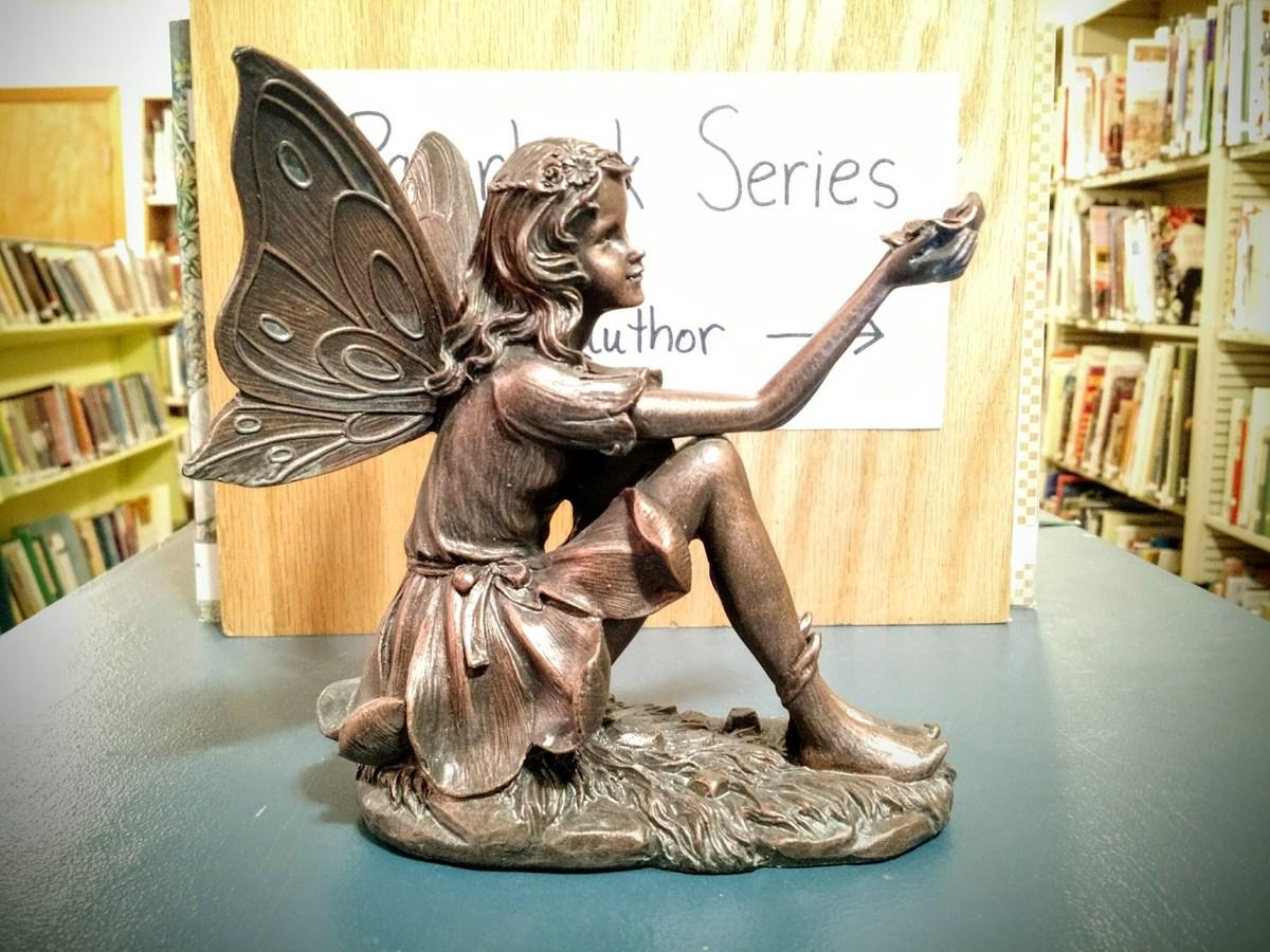 Brass Fairy Sculpture in Front of Bookshelf