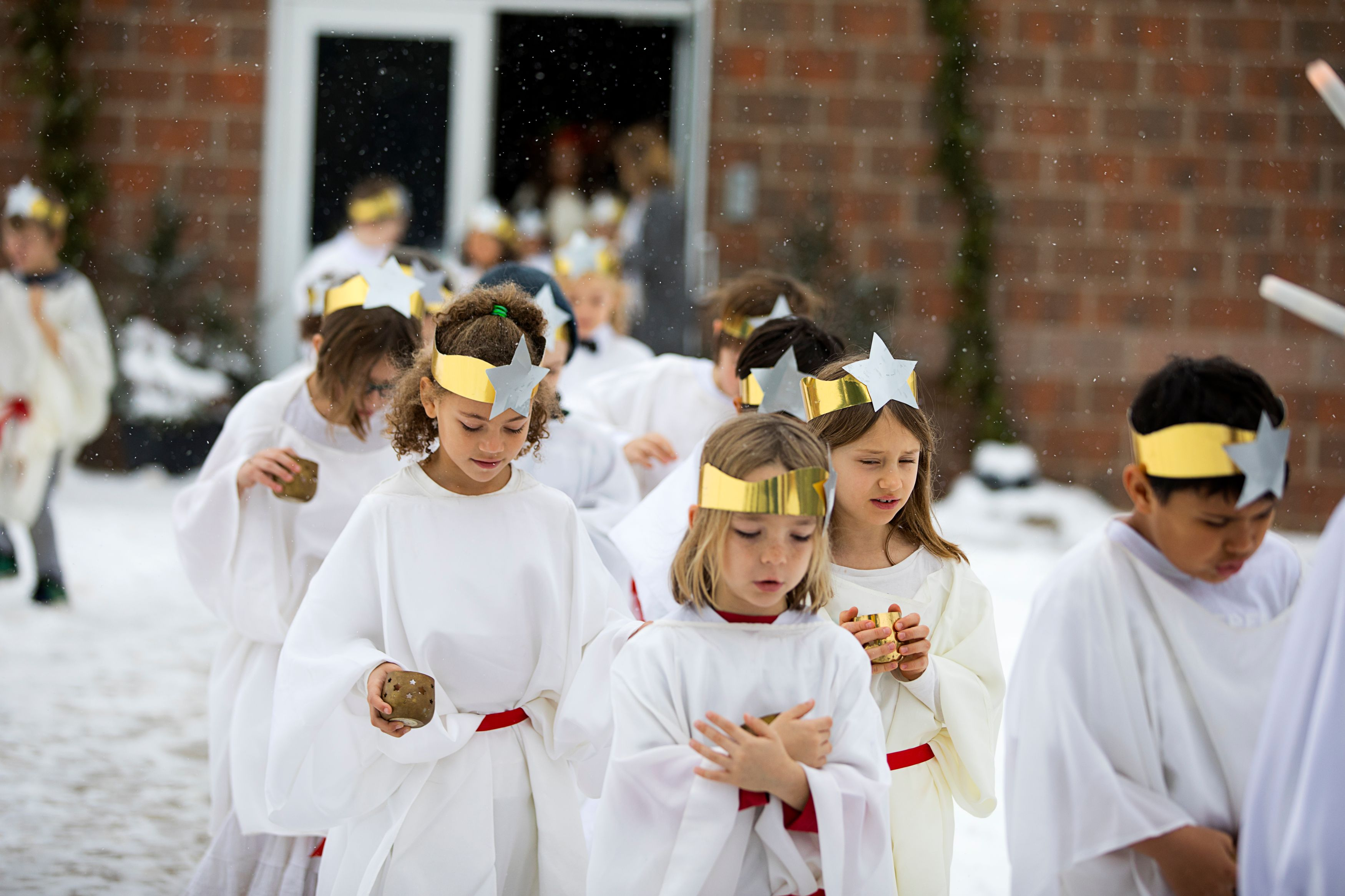 Children wearing gold headbands and white robes